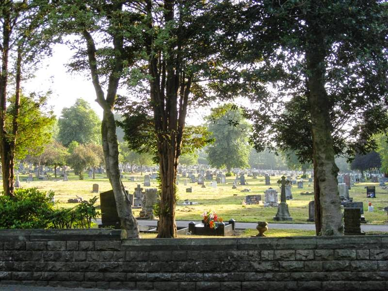 View over a low wall into a sunny cemetary