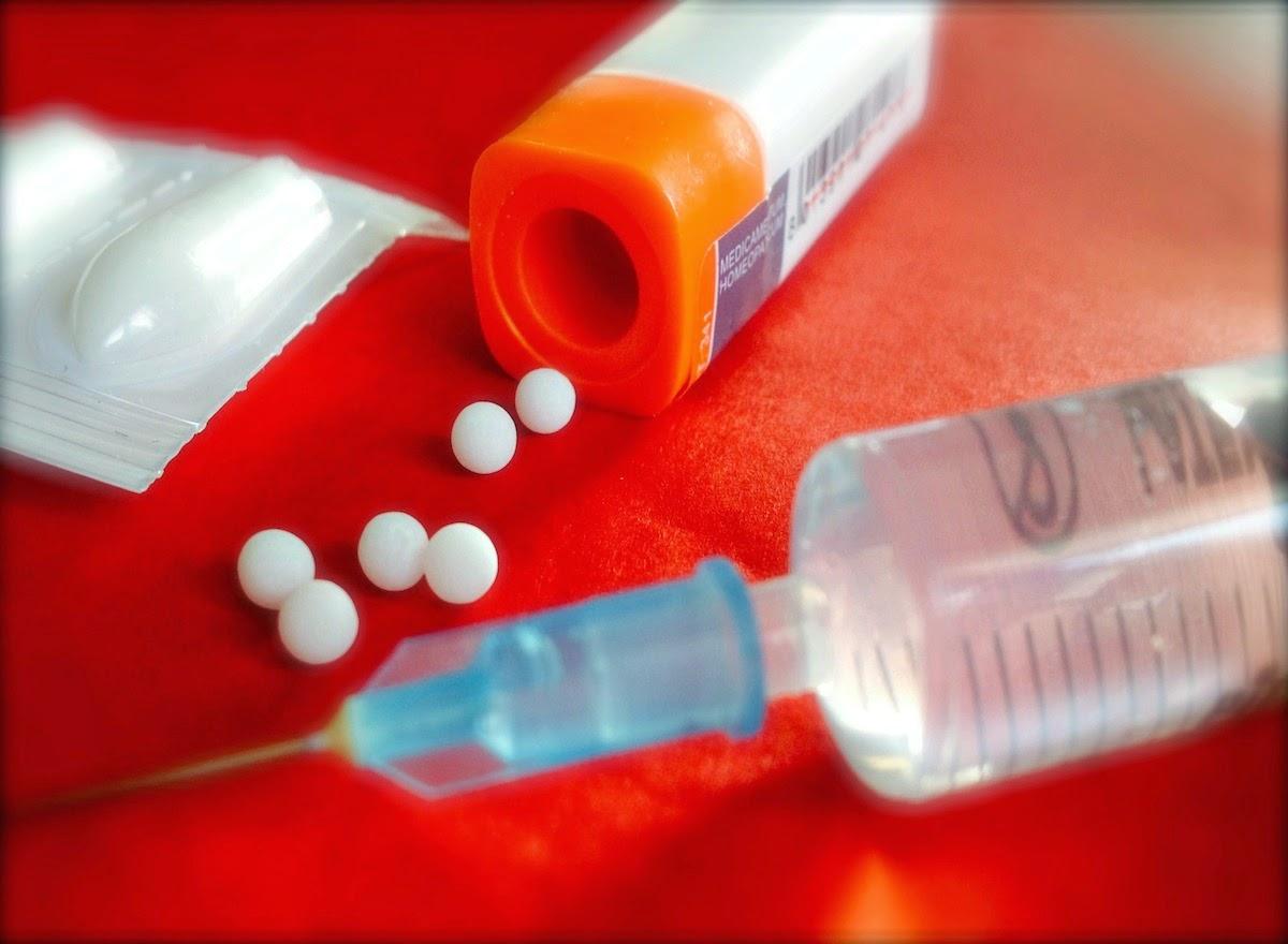 Una siringa, Una supposta, un tubo dose omeopatico con granuli omeopatici su base rossa