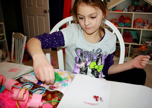 Tessa raided her craft kit for cool accessories to add to her mask. She came up with the idea of using a feather for the mouth. As a final touch, she used red glitter to color the cheeks.