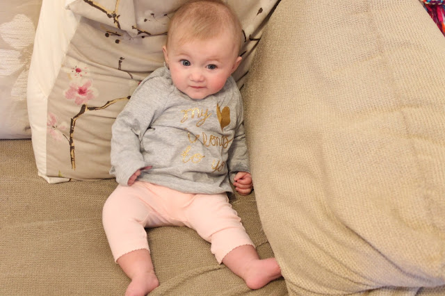 baby wearing grey long sleeved top with gold glitter writing saying my heart belongs to you and pink leggings