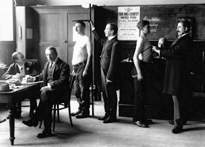 Black and white photo, WW1, a young man having his chest measured and another his height taken.  There are two men seated taking notes.  A recruiting poster is visible on the wall behind