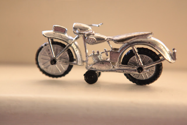 An old, silver, toy motorcycle sitting on a table.