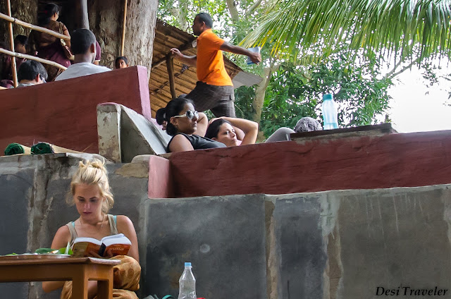 girl reading book on india under the mango tree restaurant
