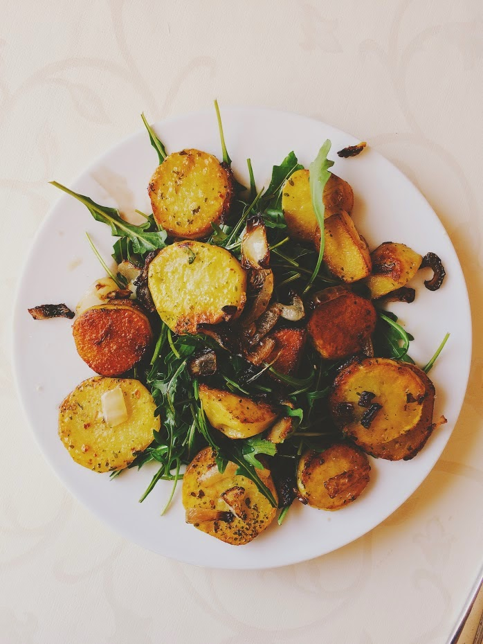 Healthy Salad with fried potatoes, onions, chilli, rucola and so on