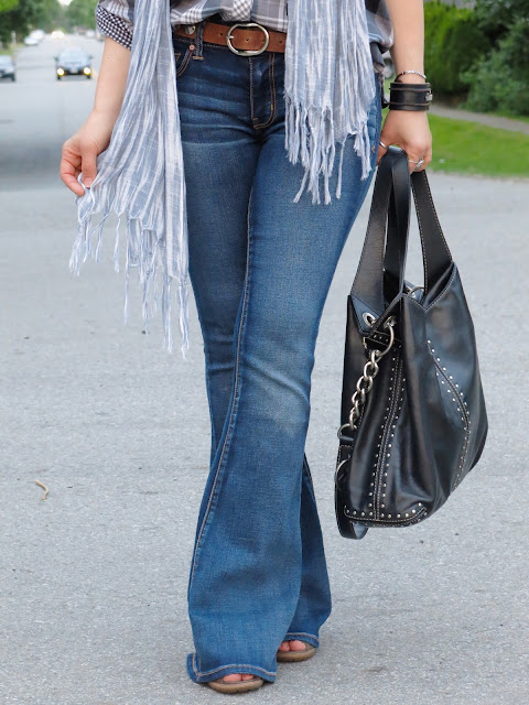 styling flare jeans with an oversized plaid shirt and a scarf