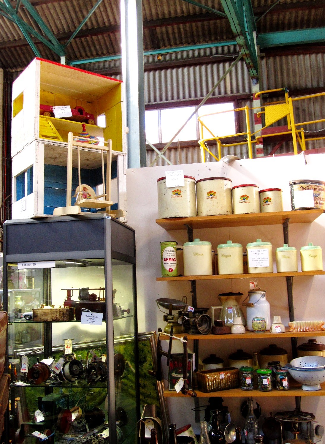 Vintage dolls house made of two packing crates on their sides, painted white on the outside and bright blue and yellow inside, displayed on the top of a tall display cabinet.