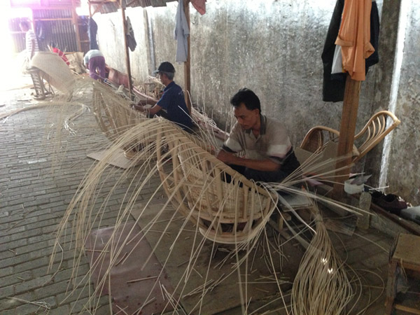 Worker in Indonesia weaving rattan through a chair