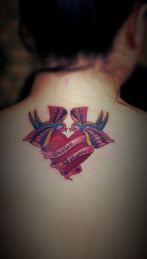 A back tattoo featuring two birds singing on a hear tattoo