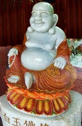 White jadeite sitting Buddha with ruby and gold dust decoration