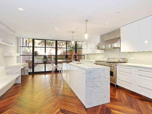 Sleek kitchen with herringbone wood floors, white drawers with long drawer pulls and cabinets, stainless appliances, pendant lights, an islance with marble countertop, and black encasement windows and door exiting to a patio