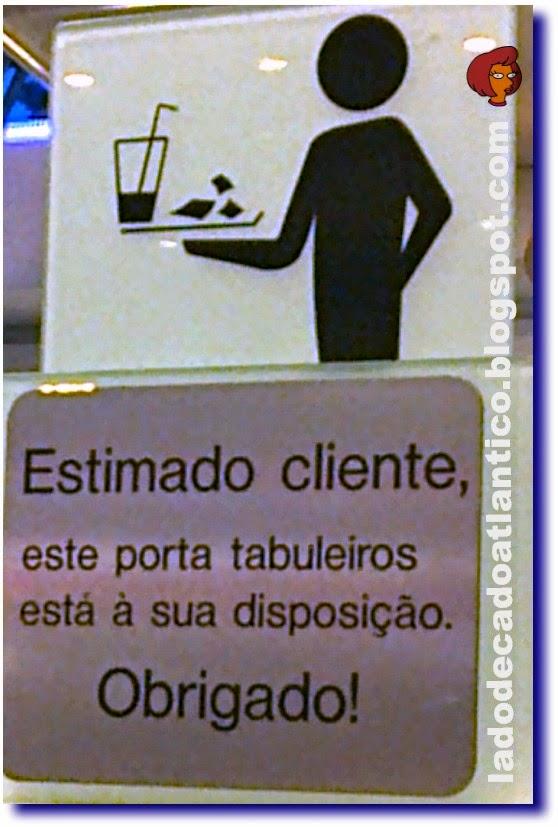Imagem de uma sinalética colocada próxima a um porta bandejas (tabuleiros) numa zona de restauração (praça de alimentação) de um centro comercial de Lisboa