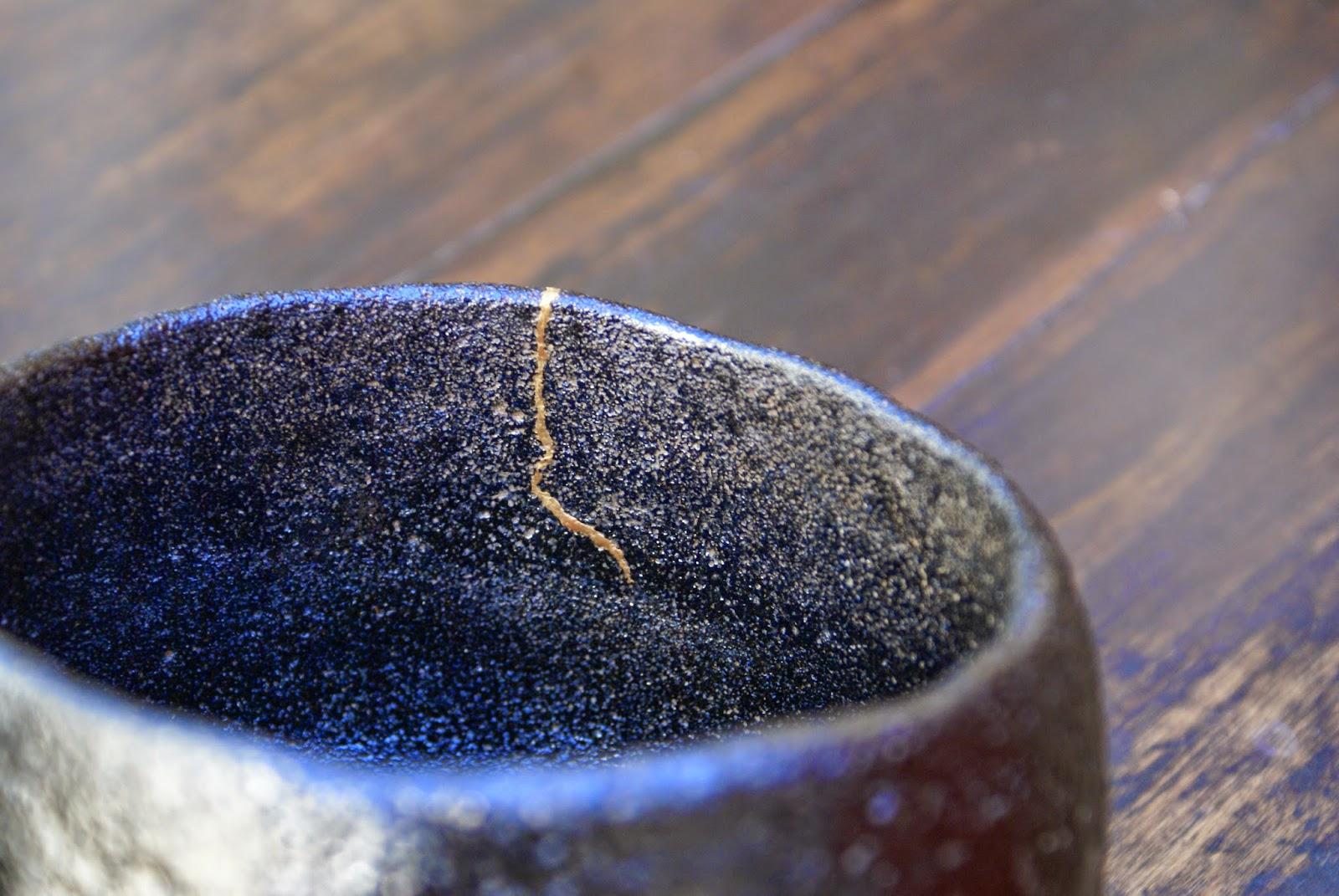 réparation à la poudre d'or kintsugi sur chawan kuro raku