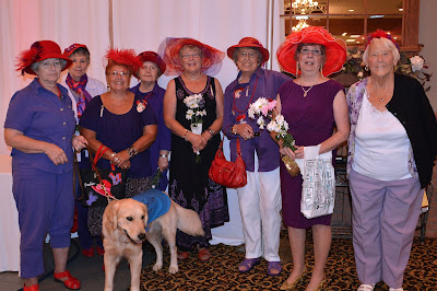 Eight ladies dressed in purple wearing fancy red hats pose with a golden retriever in front of them. The dog is 11 months old and is wearing a blue jacket stating that he is in training to be a Future Leader Dog.
