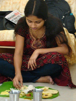 Tamil girl eating at party in traditional banana leaf.