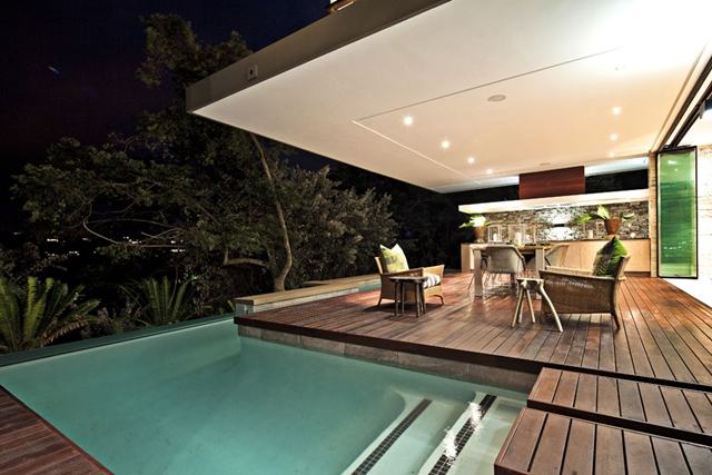 Terrace and the pool at night in the Contemporary South African SGNW House by Metropole Architects