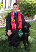 Bryan Goings in his graduation uniform with guide dog puppy