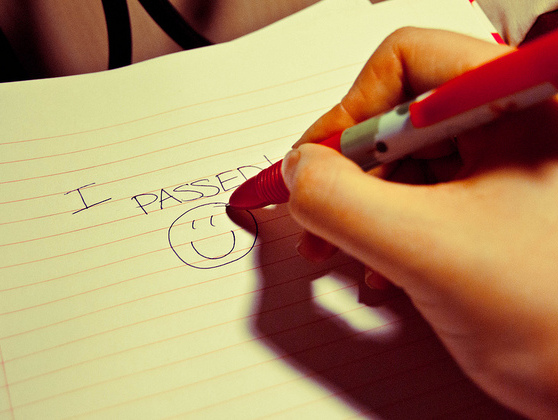 A hand writing 'I passed!' on a notebook with a smiley face