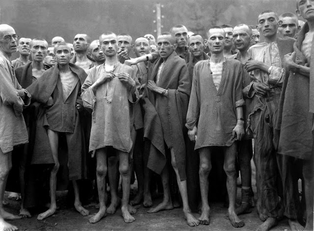 "Starved prisoners, nearly dead from hunger, pose in concentration camp in Ebensee, Austria. The camp was reputedly used for ""scientific"" experiments. It was liberated by the 80th Division. 7 May 1945. Author: Samuelson, Lt. A. E."