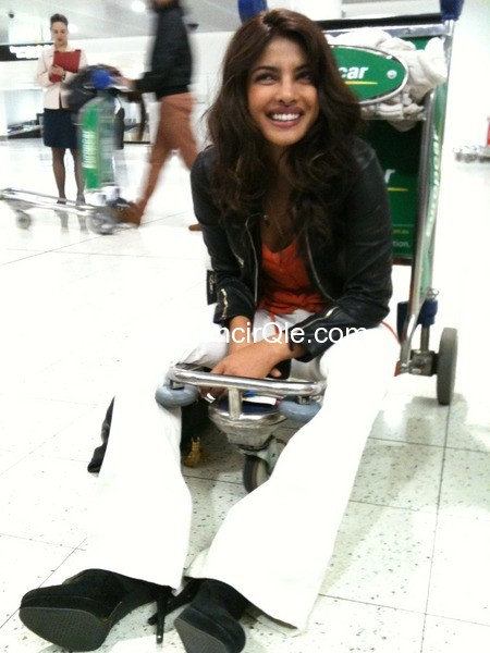 Priyanka chopra in white boot cut jeans  sitting on a cart at Melbourne Airport -  Priyanka Chopra at Melbourne airport
