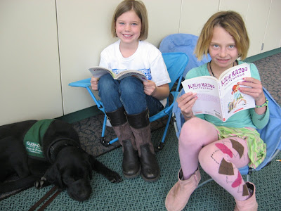 Chiffon, a GDB puppy-in-training, in her puppy coat lying on the floor while two blond girls read to her