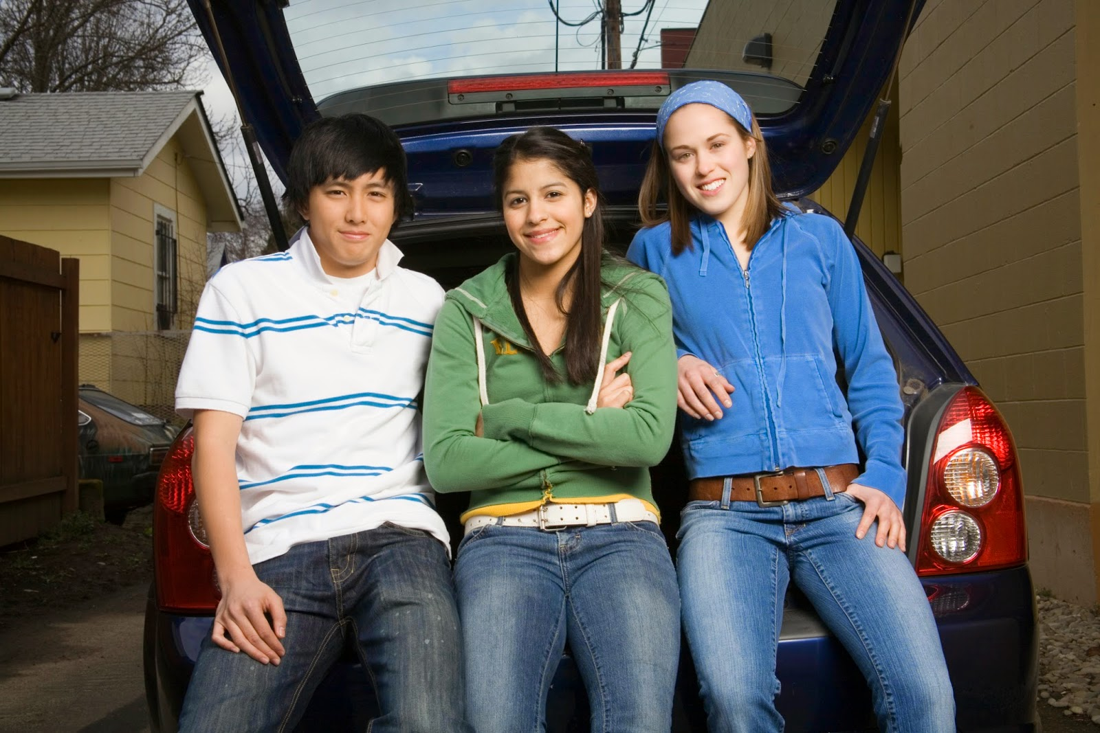 teens sitting on bumper of car