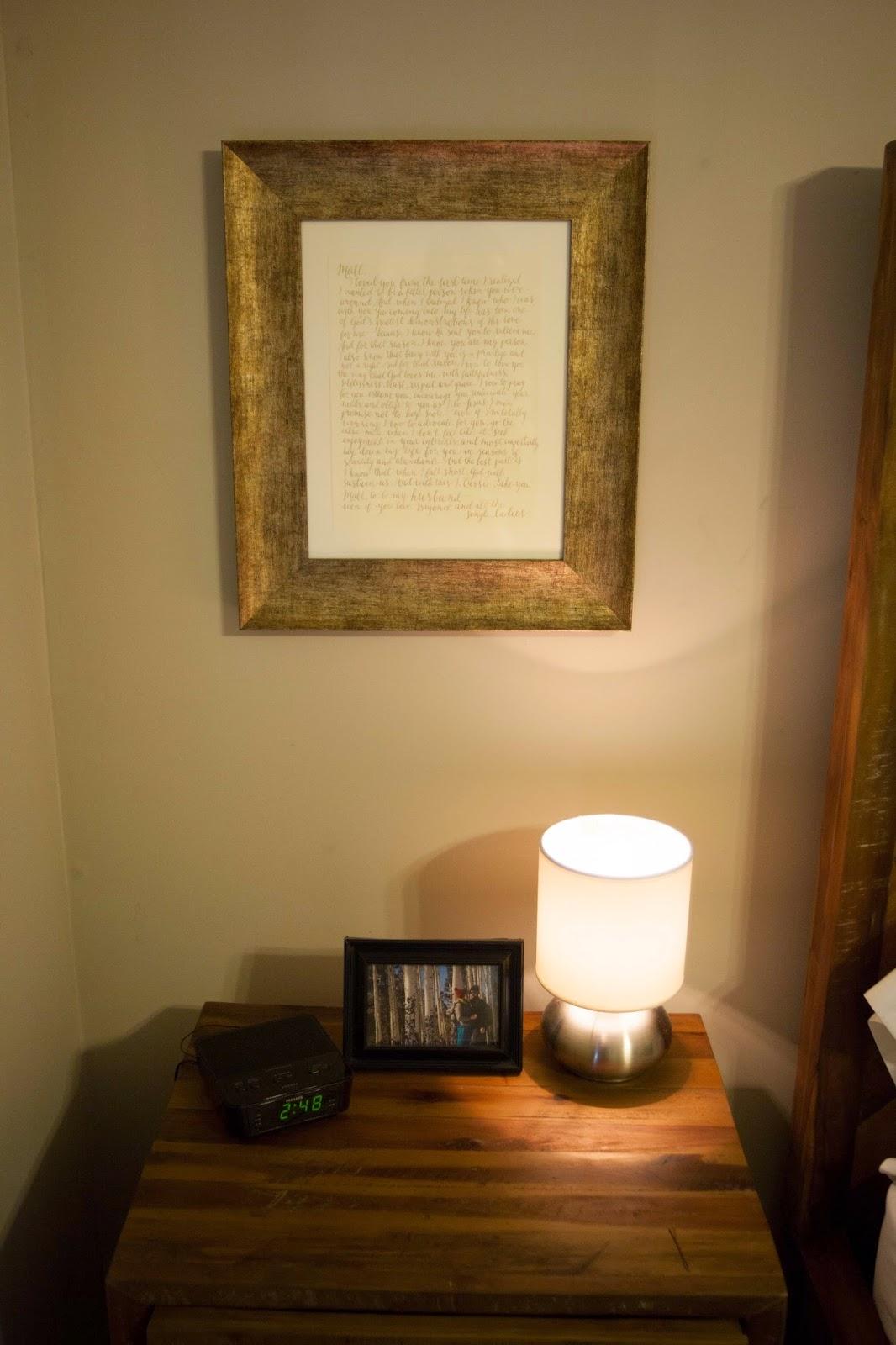 Framed wedding vows above bedside table