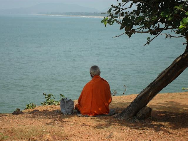 Индуисткий монах на берегу океана медитирует