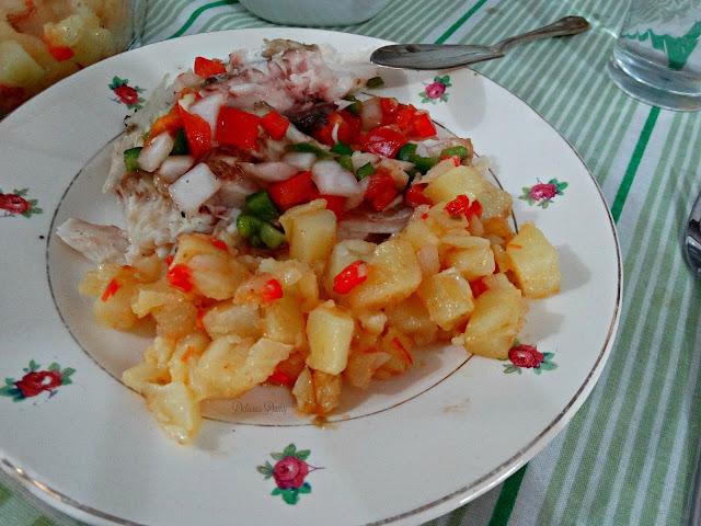 Porción de pescado y papas con salsa criolla