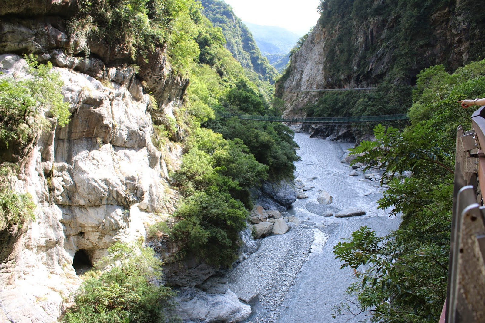 Looking at dashing stream of Liwu River while pointing at beautiful marble walls at Swallow Grotto of Taroko Gorge National Park in Hualien, Taiwan