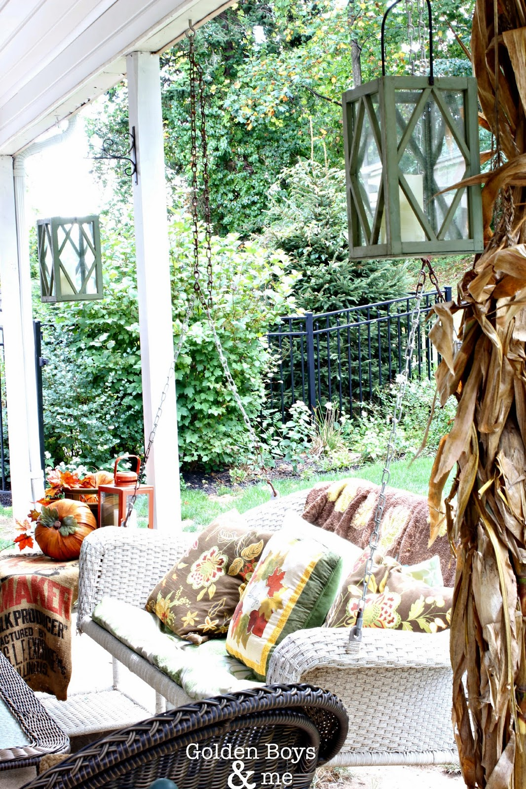 Lanterns and corn stalk as fall decor on covered patio via www.goldenboysandme.com