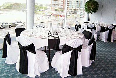 otra bella propuesta en la que se combinan centros de mesa negros y blancos paos de tela como teln de fondo y el techo que favorece desde todo punta de
