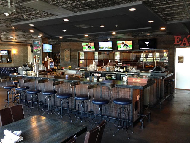 A photo of the dining area of Bosscat Kitchen and Libations, featuring a bar, dining tables, and televisions.