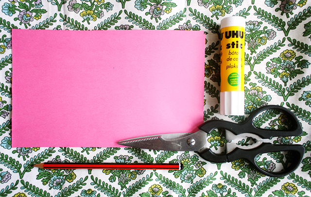 tools to make a paper bow, uhu glue stick, scissors, pencil, paper on floral background