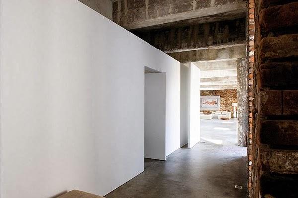 Hol minimalistycznie rządzony biała ściana, betonowa podłoga i ściany z cegły