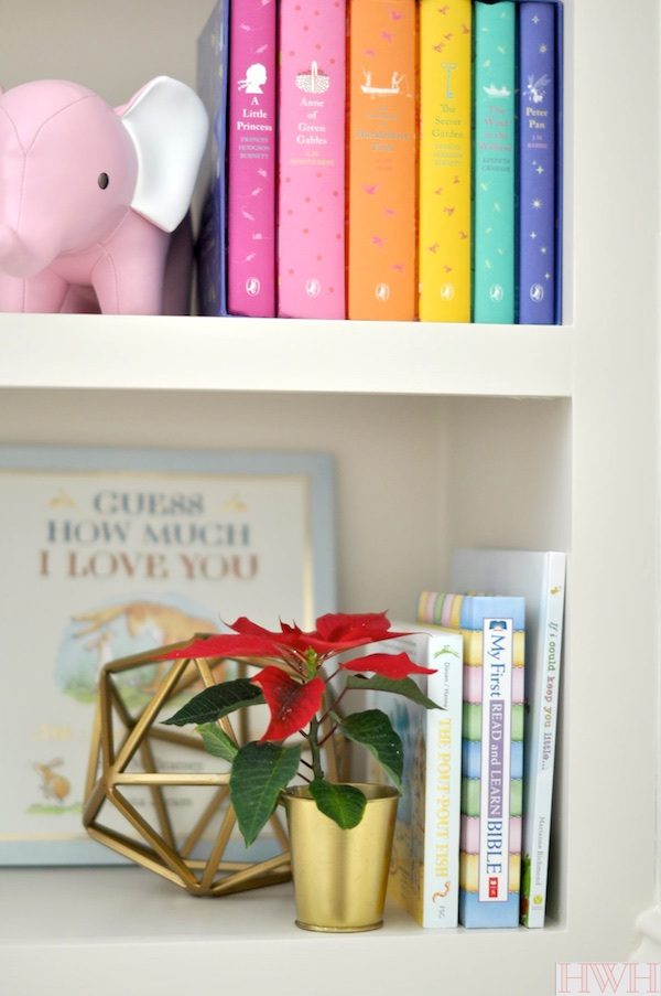 Festive holiday nursery bookshelf with pink and gold decorations. | Honey We're Home