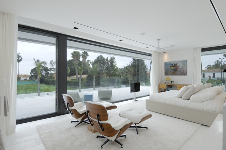 Bedroom with glass wall in Sotogrande House by A-Cero Architects