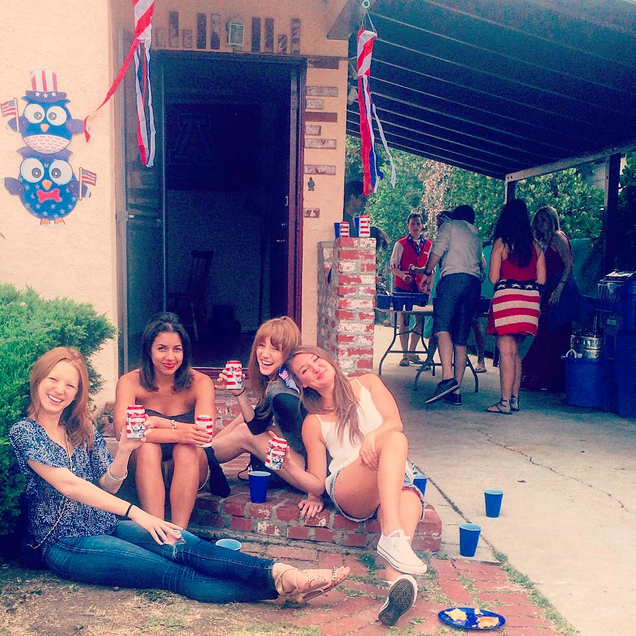 Twins and friends sitting on stairs at Independence Day party