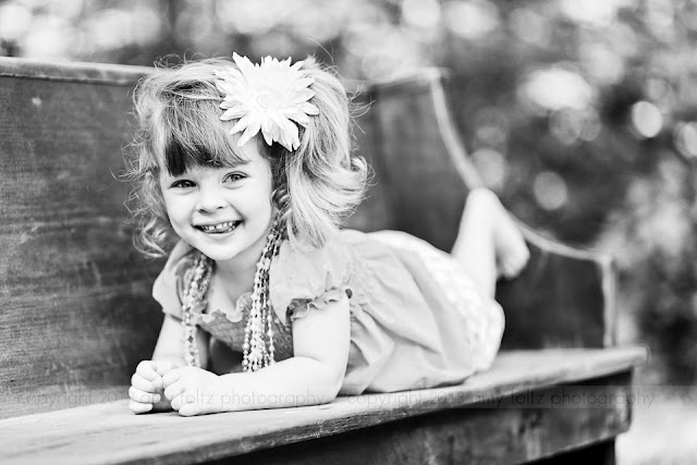 black and white photo of a little girl laying on an old church pew