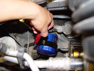 Using an oil filter strap wrench to remove an oil filter