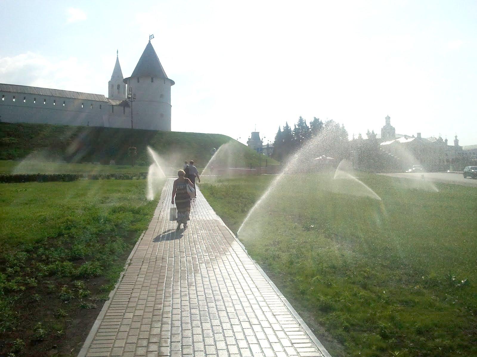 Прохожие под струями воды от газонополивалок у Казанского кремля