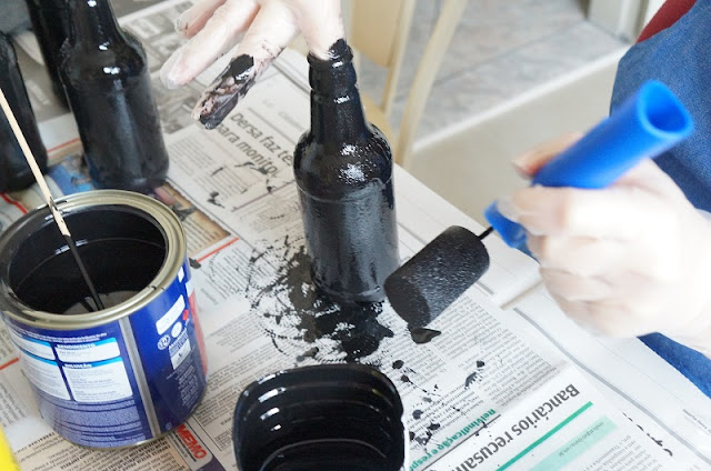 Passando o rolinho com tinta lousa nas garrafinhas
