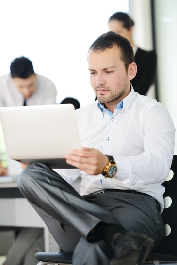 young businessman with gold watch at the laptop