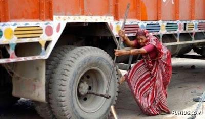 senhora trocando o pneu de um CAMINHÃO