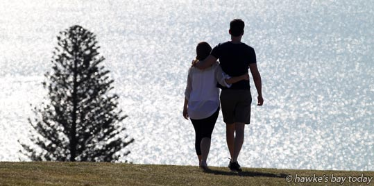 The sun reflects off the sea along Hardinge Rd, Ahuriri, Napier, as a young couple walk along the Bluff Hill Lookout, Napier, in the hot sunny summer weather. photograph