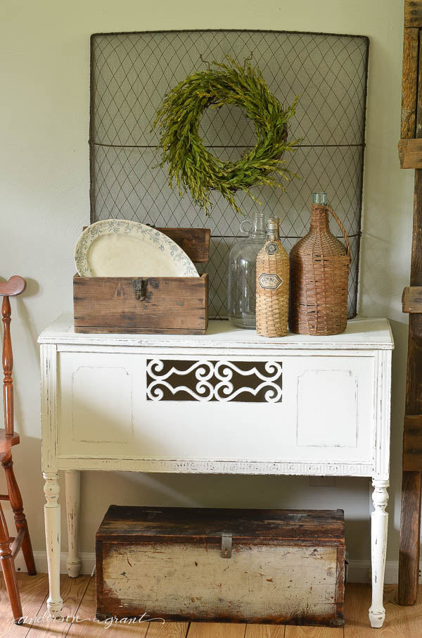 A wire mesh fireplace screen is used as a backdrop to a vignette and provides a perfect place to hang a boxwood wreath.