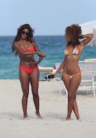 Claudia Jordan pointing at her hot friend in a bikini