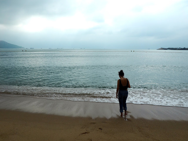 Figure of a girl paddling in the sea at Hung Shing Yeh beach, Lamma Island, Hong Kong