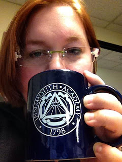 "Author with auburn hair cut to the chin, wireless glasses, holding a dark blue-purple mug in front of her mouth.  Mug reads ""Innsmouth Academy 1798"" with a stylized Illuminati symbol"