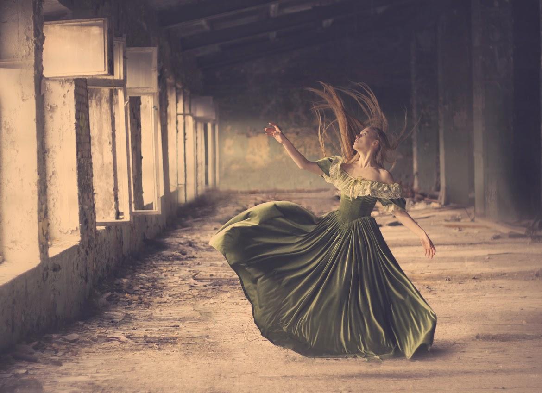 photo de Katerina Plotnikova d'une jeune femme faisant valser sa robe verte dans la poussière