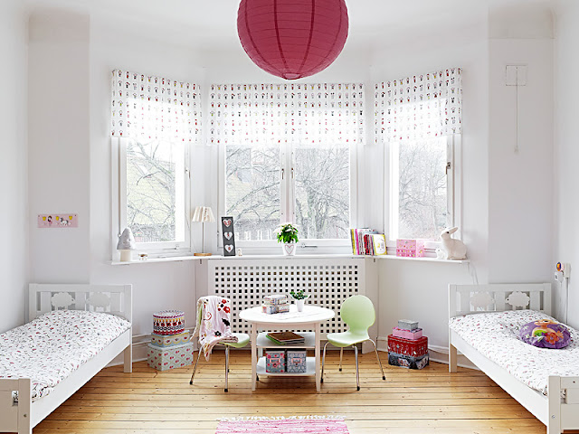 White children's bedroom with two beds with patterned bedding, pink spotted accents on the curtains, a small table with two green chairs and a large round pink lantern on the ceiling